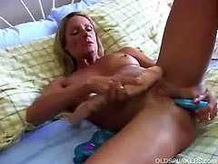 Sexy cougar in stockings lies back and fucks her wet pussy for you