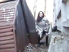 Girl in pantyhose and a skirt squats outdoors to pee and is caught on camera