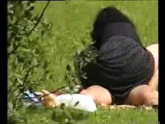 Girl in a black skirt sits on a dick in a grassy field as a voyeur spies on them