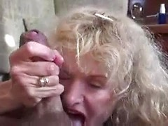 Old lady with awesome fake tits sucks and strokes a dick until it cums